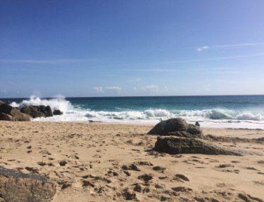 sandy-beach-and-rocks-and-crashing-waves.jpg